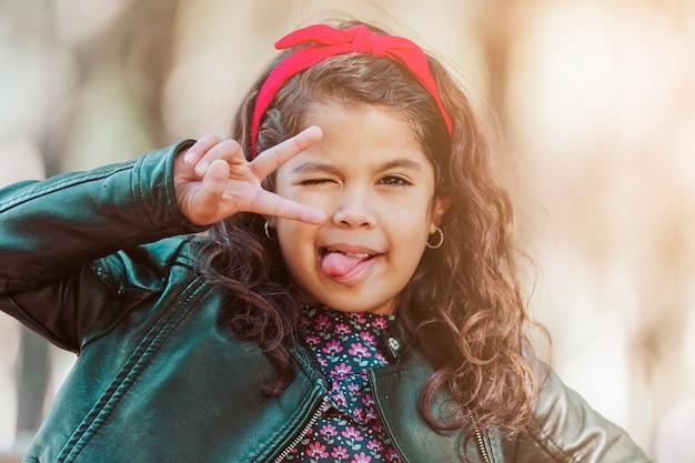 Jeune fille latine faisant le signe de la victoire avec sa main, tirant la langue et clignotant dans un parc. elle a une expression moqueuse. concept d'enfance et d'éducation