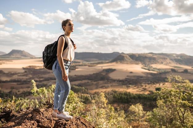 Jeune fille latine avec sac à dos profitant du coucher de soleil au sommet de la montagne