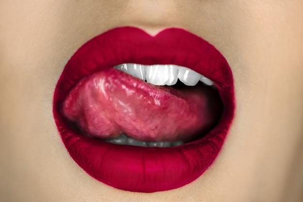 Jeune fille lèche sexuellement ses lèvres rouges