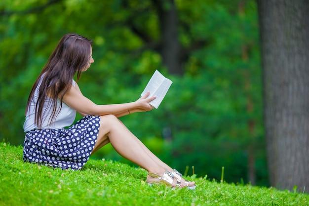 Jeune fille, lecture livre, dehors, dans parc
