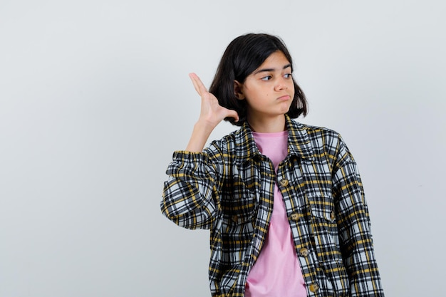 Jeune fille levant la main comme parlant à quelqu'un via un téléphone portable en chemise à carreaux et t-shirt rose et ayant l'air sérieux