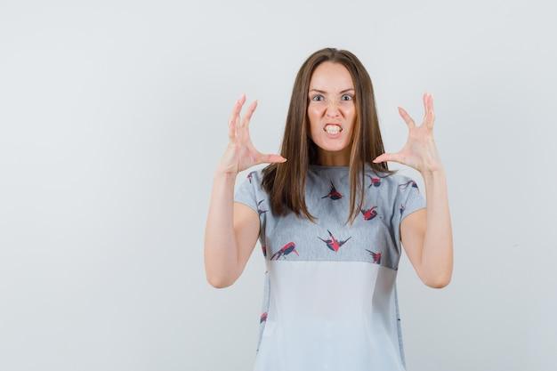 Jeune fille levant les mains de manière agressive en t-shirt et à la furieuse, vue de face.