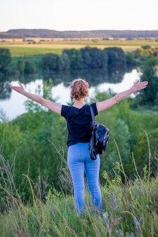 Une jeune fille a levé les mains appréciant l'unité avec la nature_