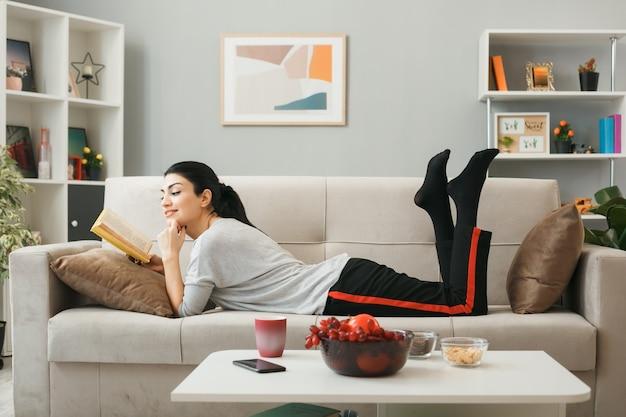 Jeune fille lisant un livre allongé sur un canapé derrière une table basse dans le salon