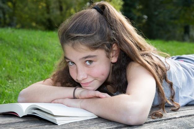 Jeune fille lisant un livre au parc couché sur un banc