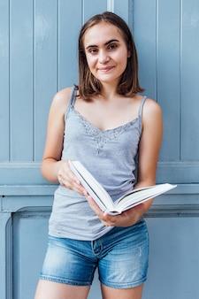 Jeune fille lisant un livre sur fond gris bleu