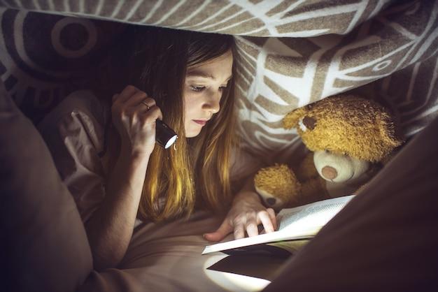 Jeune fille lisant un livre magique dans le noir