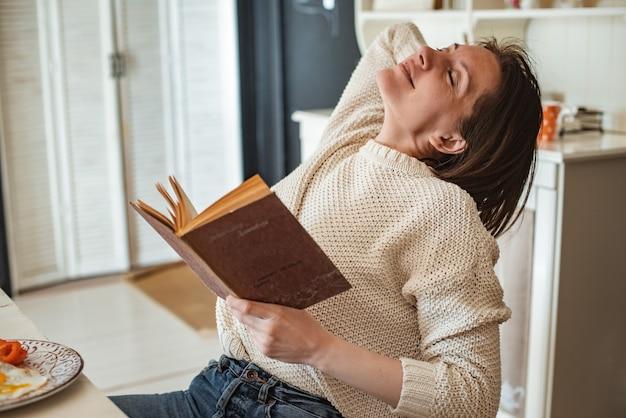 La jeune fille lit un vieux livre au petit déjeuner. gros plan sur les mains et le réglage de la table. style campagnard. oeufs brouillés et légumes frais et lecture d'un livre intéressant le matin