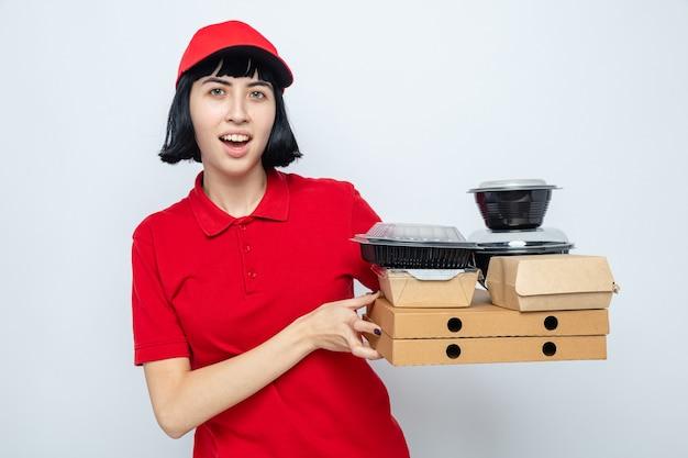 Jeune fille de livraison caucasienne impressionnée tenant des récipients alimentaires et des emballages sur des boîtes à pizza