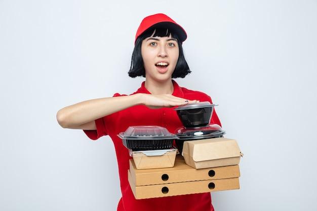 Jeune fille de livraison caucasienne surprise tenant des contenants de nourriture et des emballages sur des boîtes à pizza