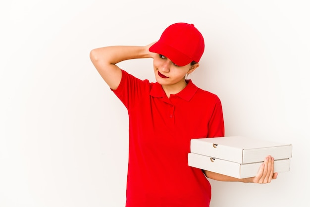 Jeune fille de livraison de pizza arabe maigre montrant un espace de copie sur une paume et tenant une autre main sur la taille.