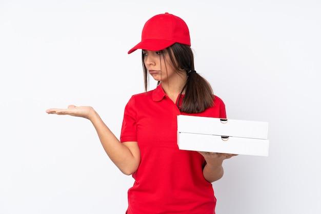 Jeune fille de livraison de pizza sur fond blanc isolé holding copyspace avec des doutes