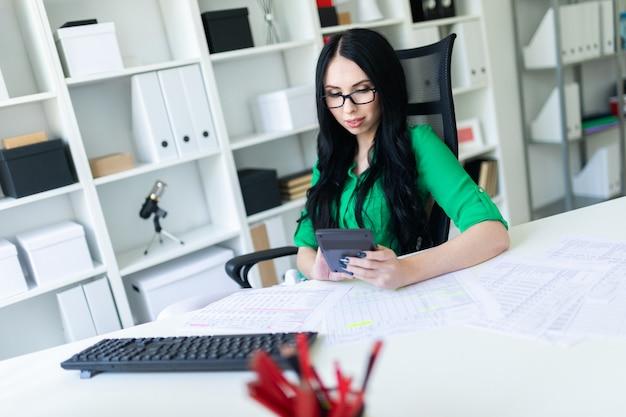 Une jeune fille avec des lunettes au bureau compte sur une calculatrice.