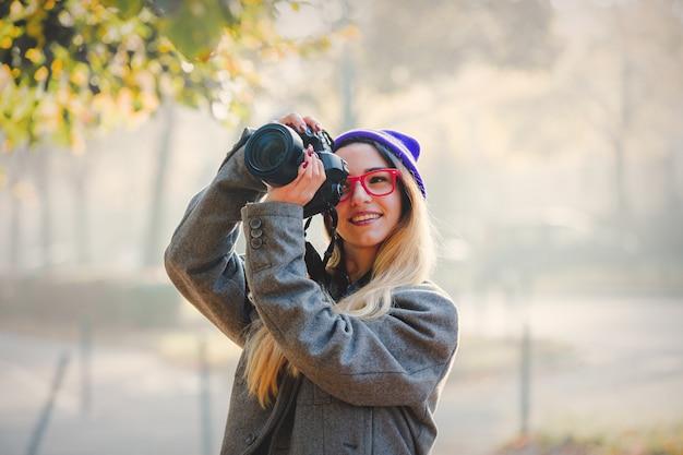 Jeune fille à lunettes et bonnet avec caméra