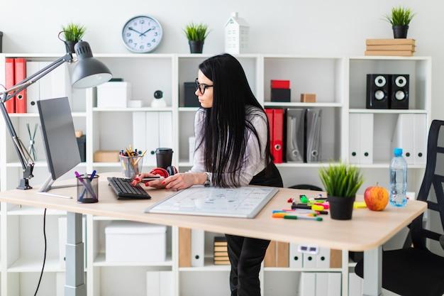 Une jeune fille à lunettes se tient près de la table, tient un marqueur dans sa main et imprime sur le clavier.