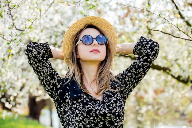 Jeune fille à lunettes de soleil et chapeau reste près d'un arbre en fleurs