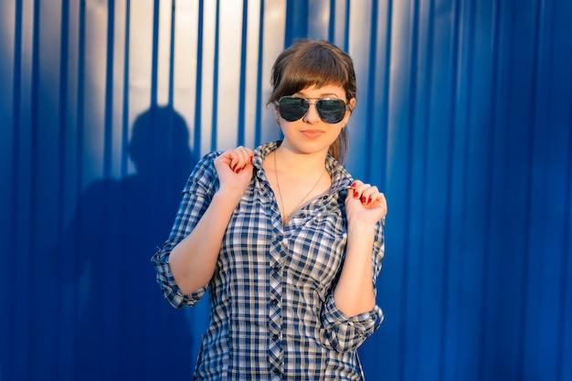 Jeune fille à lunettes de soleil en chemise
