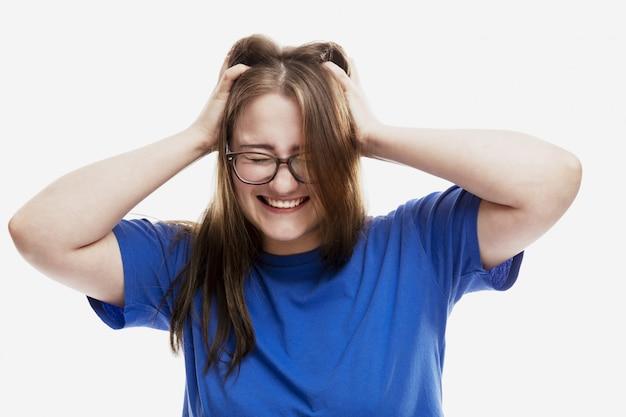 Une jeune fille à lunettes tient sa tête et rit.