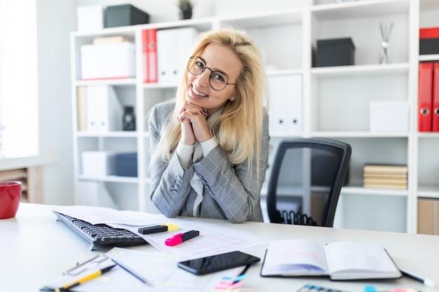 Jeune fille à lunettes travaille au bureau.