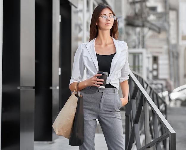 Jeune fille magnifique portant des sacs en papier, sortant du magasin.