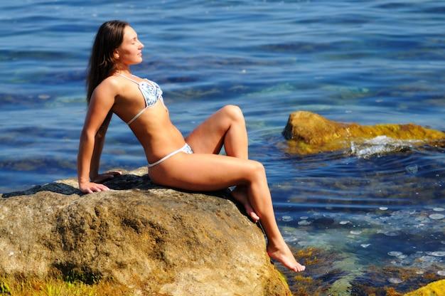 Jeune fille en maillot de bain blanc et bleu posant les yeux fermés, assis sur un gros rocher près de la mer