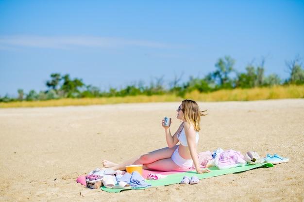 Une jeune fille en maillot de bain blanc sur une journée ensoleillée sur une plage de sable est assise sur un tapis avec une tasse à la main et des boissons