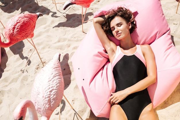 Jeune fille en maillot de bain couché et se faire bronzer sur un gros oreiller rose à côté de flamants roses sur la plage. portrait de belle fille fermant les yeux rêveusement tout en passant du temps sur la plage