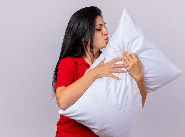 Jeune fille malade caucasienne étreignant l'oreiller faisant le geste de baiser avec les yeux fermés isolé sur fond blanc avec copie espace