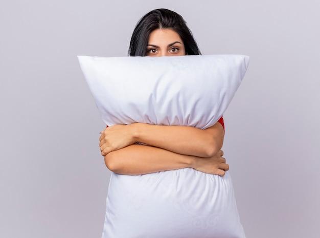 Jeune fille malade caucasienne hugging oreiller regardant la caméra par derrière elle isolé sur fond blanc avec copie espace