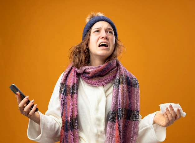 Jeune fille malade en colère portant une robe blanche et un chapeau d'hiver avec foulard tenant le téléphone et la serviette étalant les mains isolés sur le mur orange