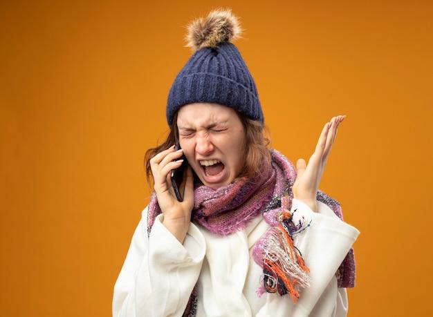 Jeune fille malade en colère avec les yeux fermés portant une robe blanche et un chapeau d'hiver avec écharpe parle au téléphone répandant la main isolé sur orange