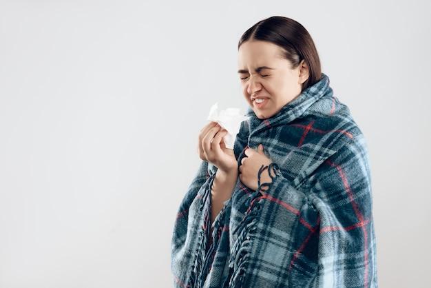 Jeune fille malade couverte dans la couverture éternue.
