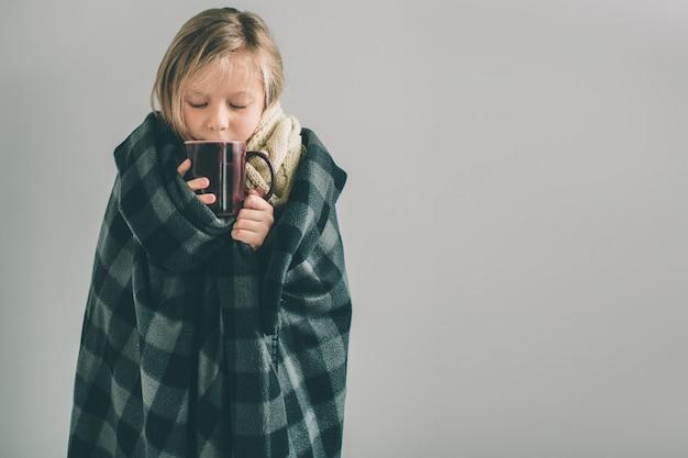 Jeune fille malade avec couverture et boisson chaude