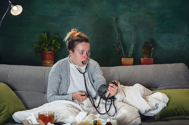 Jeune fille malade avec fièvre et froid semble souffrir.