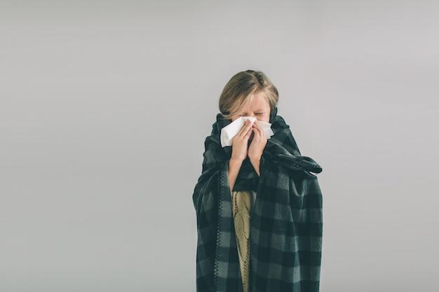 Jeune fille malade avec mouchoir et couverture