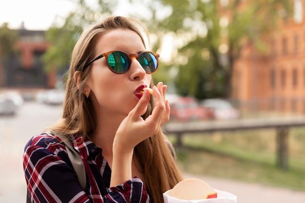 Une jeune fille mange ses frites directement dans la rue. elle a très faim, un appétit brutal s'est réveillé en elle.