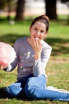 Jeune fille mangeant de la barbe à papa dans le parc