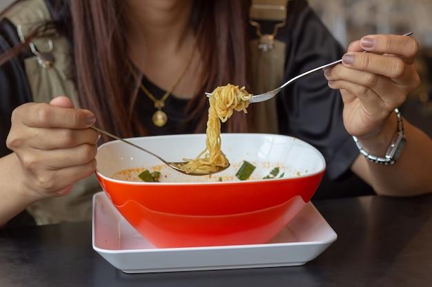 Jeune fille mangeant des nouilles, déjeuner à la hâte, tom yum noodles