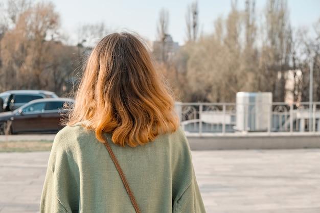 Jeune fille marchant en arrière avec les cheveux roux en pull vert