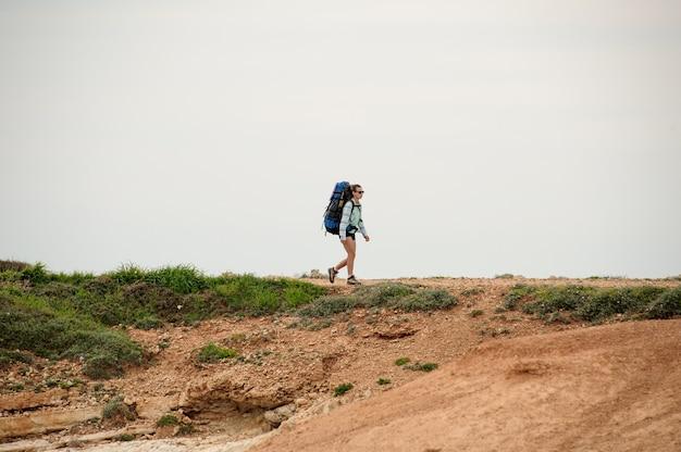 Jeune fille marchant sur la côte en chemise et lunettes de soleil avec un sac à dos
