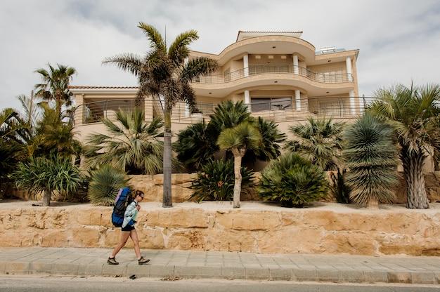 Jeune fille marchant devant la maison en chemise et lunettes de soleil avec un sac à dos