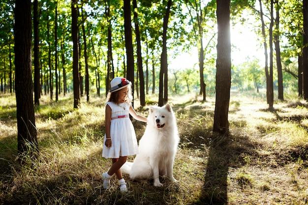 Jeune fille marchant, jouant avec un chien dans le parc au coucher du soleil.