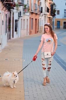 Jeune fille marchant avec un poméranien moelleux blanc.