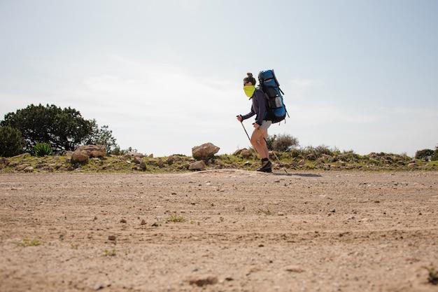 Jeune fille marchant avec un sac à dos de randonnée et des bâtons dans un masque spécial de la poussière
