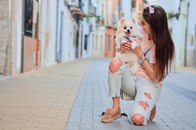 Jeune fille marchant avec son poméranien moelleux blanc.