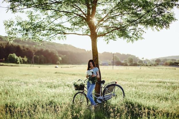 La jeune fille marche avec un chiot dans un champ de vélo à l'arrière de la lumière du soleil