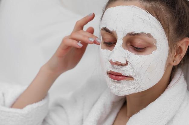 Jeune fille avec masque facial. soin de la peau. belle jeune fille se détendre avec des masques faciaux sur fond blanc