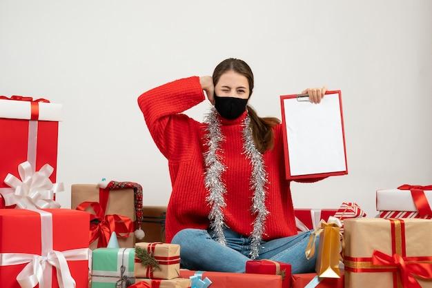 Jeune fille avec masque noir tenant des documents couvrant son oreille assis autour de cadeaux sur blanc