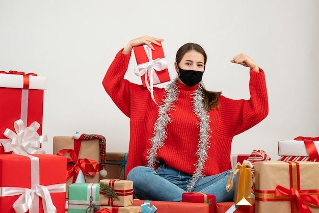 Jeune fille avec masque noir tenant présent montrant son muscle assis autour de cadeaux sur blanc