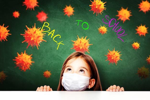 Jeune fille avec masque de protection contre le virus corona à l'école.